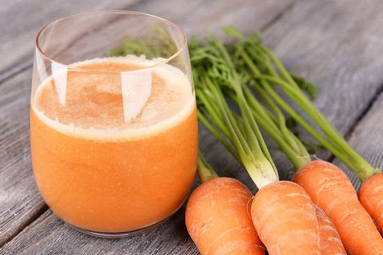 Glass of carrot juice and fresh carrots on wooden background